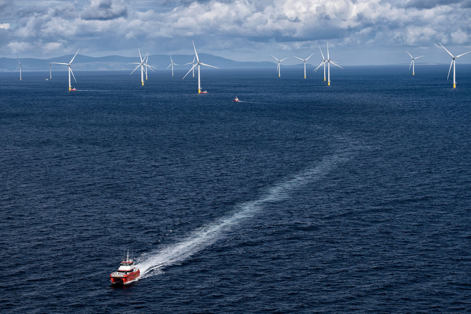 Maintenance ships tending to Hornsea Projects wind farm array in the North Sea, England.